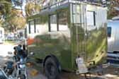 Photo shows rear end of 1929 REO Camping Wagon camper, with entry door and ladder up to roof top luggage rack