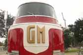 Front view of imposing 1941 GM Futurliner bus, showing bold GM block letters