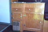 Picture of beautiful birch wood kitchen cabinets with heater and stovetop in interior of super rare 1941 Western Flyer motor home