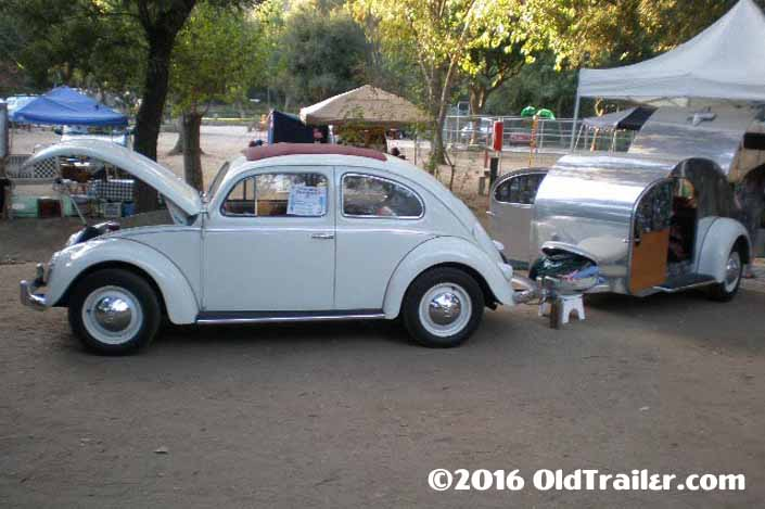 This vintage towing rig is a volkswagen bug pulling a 1947 teardrop vintage trailer