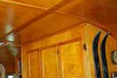 Photo of warm and glowing cabinetry and paneling in vintage 1948 Westwood Coronado trailer