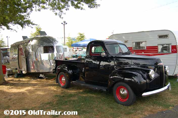 This vintage towing rig is a studebaker pickup truck pulling a 1949 curtis wright vintage trailer