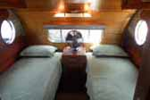 Warm and inviting rear bedroom with twim beds in a 1950 Airfloat vintage travel trailer