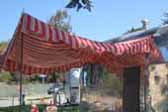Red, white and green striped side awning on a 1951 Airstream Cruisette trailer