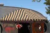 Photo of chocolate brown striped awning with brown fringe over entry door on a 1952 Airfloat vintage trailer