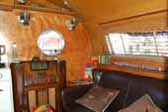 Period furnishings, vintage accessories and a comfy couch in a vintage 1952 Airfloat trailer