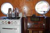 Great vintage gas stove and console radio in wood cabinet, in a restored 1952 Airfloat travel trailer