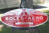 Cool large reproduction Boles Aero factory id plate next to a 1952 Boles Aero Montecito trailer