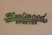 Original Fleetwood Sporter cast logo badge on the side of a vintage 1953 Fleetwood Sporter trailer