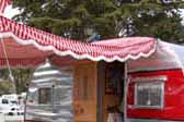 Picture of 1954 Dalton vintage trailer with a red and white peppermint striped canvas side awning