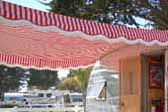 Close up picture of a 1954 Dalton vintage trailer with a red and white striped awning