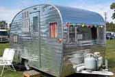 Restored 1955 Aloha travel trailer with beautifully polished aluminum exterior skin