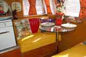 Photo shows sunny yellow dining area in a 1955 Shasta Trailer