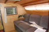 Photo of gorgeous wood paneling and beautifully upholstered couch in 1956 Campmaster Teardtop trailer