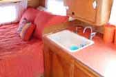 Warm and cozy bedroom area in a classic 1955 Shasta travel trailer