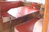 Red and white reupholstered bench seating in 1956 Shasta Trailer dining area