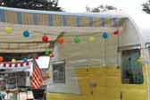 1957 Shasta vintage trailer with sky blue and lemon yellow striped canvas awning with white fringe