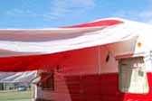 Wide red and white striped side awning on a 1957 Shasta vintage trailer