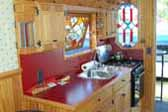 Very inviting kitchen in a 1959 Federal truck based camper features laminate countertop and tilt-out custom stained glass window