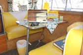 Sunny yellow dinette seats in dining area in 1959 Shasta Airflyte Trailer