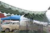 1960 Airstream Caravel trailer with a dark green and light green striped canvas awning