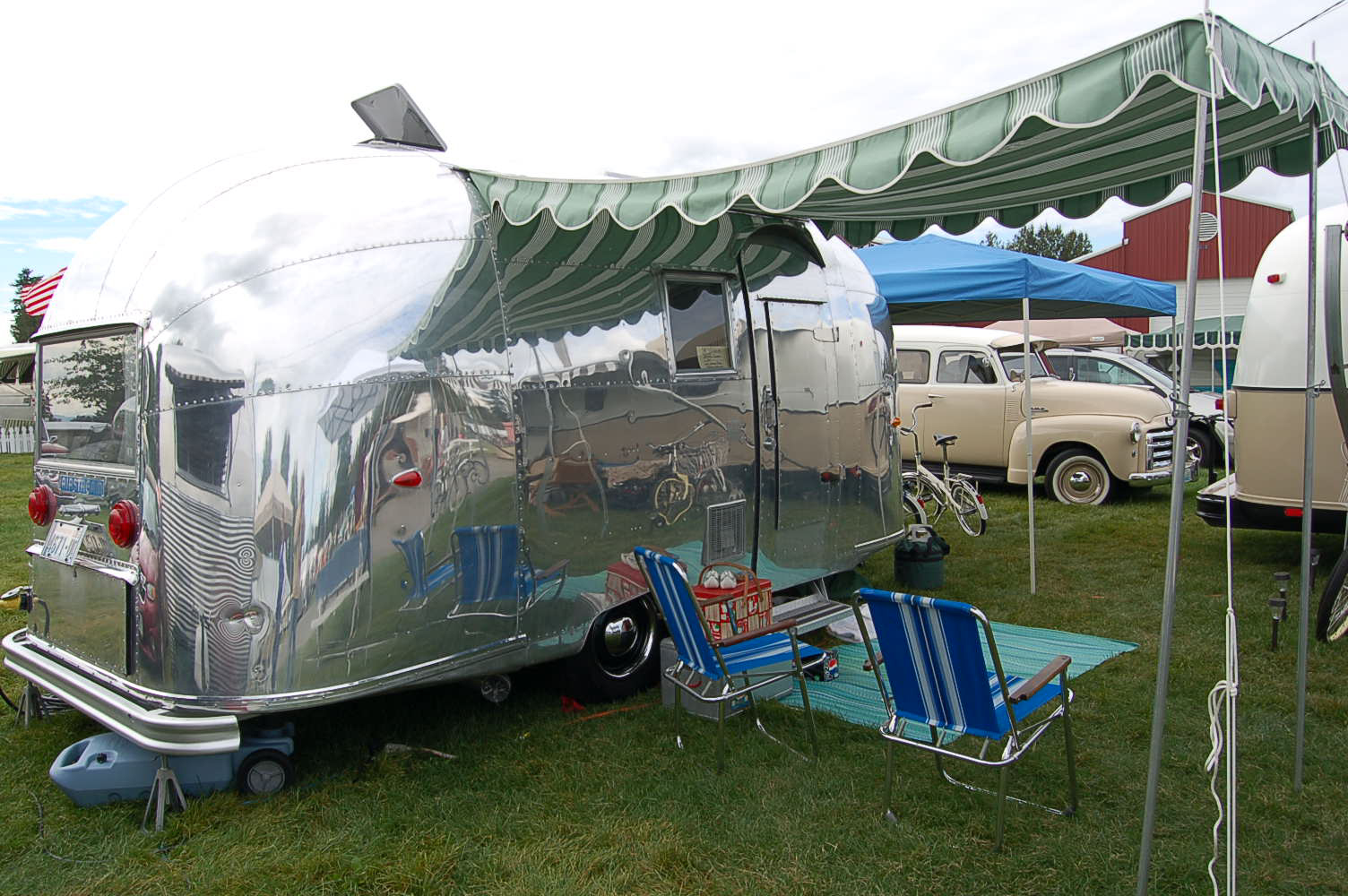 1960 Airstream Caravel Trailer With A Dark Green And Light Striped Canvas Awning