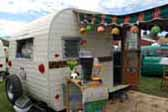 Vintage 1960 Aloha 15-ft trailer and tiki bar with green striped canvas awning and large flower hanging lights