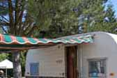 classic red, orange and green striped awning with scalloped edging on a 1960 Aloha 15ft vintage trailer