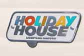 Vintage 1961 Holiday House travel trailer with an original Holiday House cast logo badge on the side