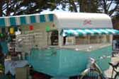 Photo of a 1961 Shasta vintage trailer with turquoise and white striped front and side awnings