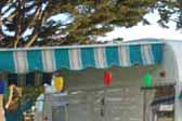 Turquoise and white striped awning with a turquoise scalloped border, on a 1961 Shasta vintage trailer