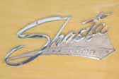 Re-chromed cast Shasta logo script emblem on the side of a 1962 Shasta Compact vintage trailer