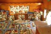 1962 Shasta Trailer with honey gold paneling and colorful retro cowboy-theme comforter