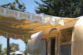 Yellow, brown and white striped side awning on a 1963 Airstream Flying Cloud trailer painted mustard yellow and white