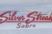 Silver Streak Sabre logo script decal in red, from El Monte Calif, on a vintage 1963 Silver Streak Sabre trailer