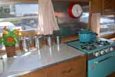 Photo shows the kitchen cabinets and interior of an Aladdin vintage trailer, the small Genie model