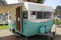 Photo of a vintage 1964 Shasta trailer showing new metal screen door and front profile first introduced in 1958