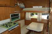 Interior photo shows the kitchen countertop, wood work and dining area in an old Aladdin travel trailer - model Genie