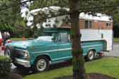 Photo of an original 1968 Ford Pickup truck out camping with a classic Chinook Camper shell mounted in the bed