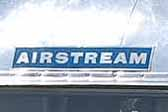 Vintage Airstream travel trailer with the famous Aitrstream blue logo graphics decal on the front