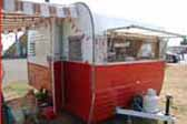Picture shows a very clean vintage Aloha travel trailer painted in classic red and white color scheme
