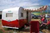Striped canvas side awning and chili pepper lights on red and white restored Aloha travel trailer