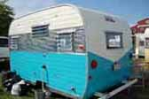 Photo of Aloha trailer with blue and white paint and polished quilted aluminum skin panel