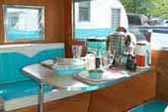 Photo of restored dinette area with blue and white upholstered bolsters in Aloha trailer