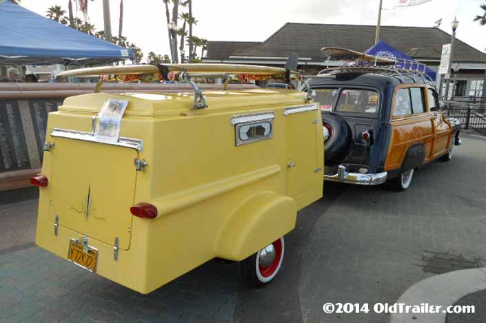 This vintage towing rig is a classic ford woodie station wagon pulling a vintage trailorboat trailer