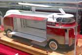 Photo of a detailed scale model of a GM Parade of Progress Futurliner bus with the roof light bar raised and the side panels open to showcase the exhibits inside