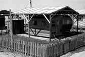 Government photo shows a 1940's vintage travel trailer with an attached wooden shack at the Project Hanford Trailer City