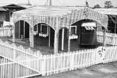 Historical photo of a 1940's worker's trailer, surrounded by a beautiful white picket fence, at Project Hanford Trailer City