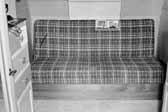 Old photo shows the plaid couch in a 1940's Government Model Trailer, at the Hanford Trailer Camp