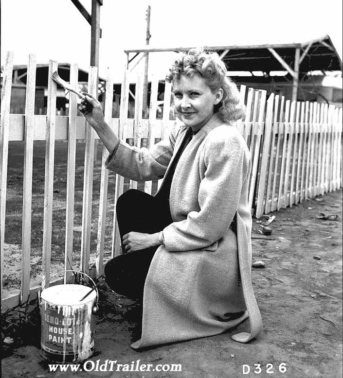 Government photo shows a pretty woman dressed up and painting her picket fence, at the Hanford Trailer Camp in Washington